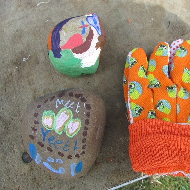 Two painted stones and a child's gardening glove