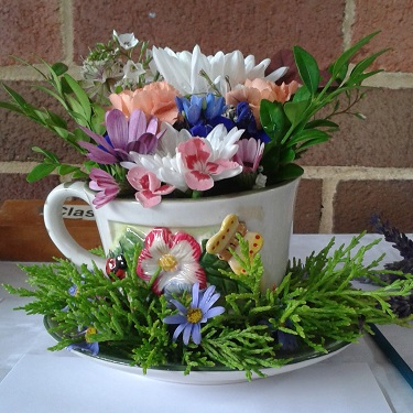 A flower arrangement in a tea cup and saucer